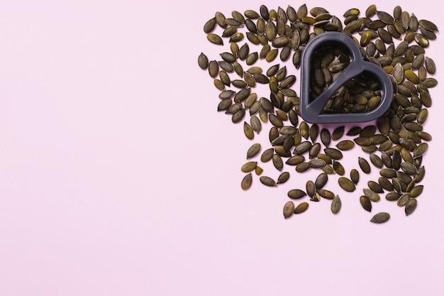 Fondo rosa. semillas de calabaza en la esquina derecha y un cortador de galletas en forma de corazón. espacio vacío para publicidad.