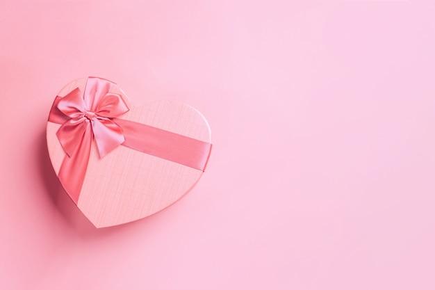 Fondo rosa de vacaciones románticas con caja de regalo en forma de corazón. tarjeta decorativa para el día de san valentín con espacio para texto.