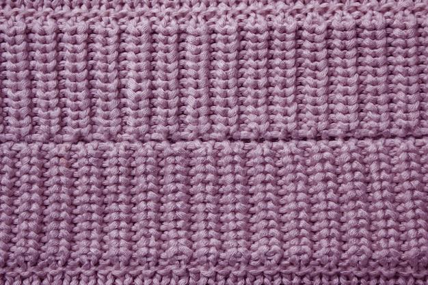 Fondo rosado de la textura de las lanas que hace punto.