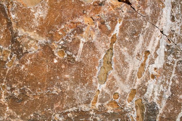 Fondo rufo del grunge pedregoso natural con la grieta y las manchas blancas.