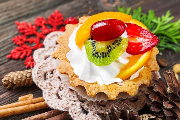 Fondo rústico de vacaciones de invierno con tarta de frutas y especias - canela, anís, maní.