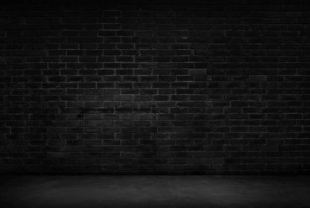 Fondo de la sala de pared negra la superficie de la oscuridad de ladrillo irregular. fondo de habitación vacía de pared negra abstracta para diseño de interiores y decoración.