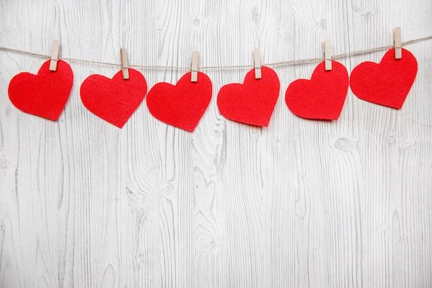 Fondo de san valentín con borde de fila de corazones rojos en pinzas para la ropa en madera blanca. lugar para el texto, lugar para copiar.
