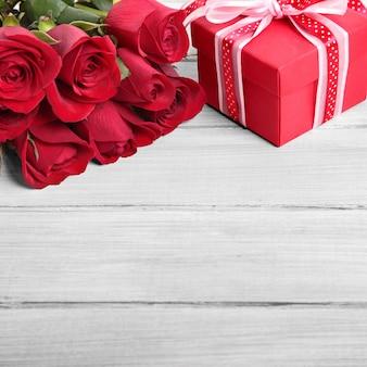 Fondo de san valentín de caja de regalo y rosas rojas en madera blanca