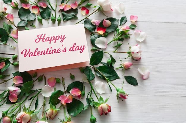 Fondo de san valentín con círculo de flores rosas rosadas y tarjeta de papel hecho a mano con espacio de copia en madera rústica blanca. maqueta de feliz día de los enamorados