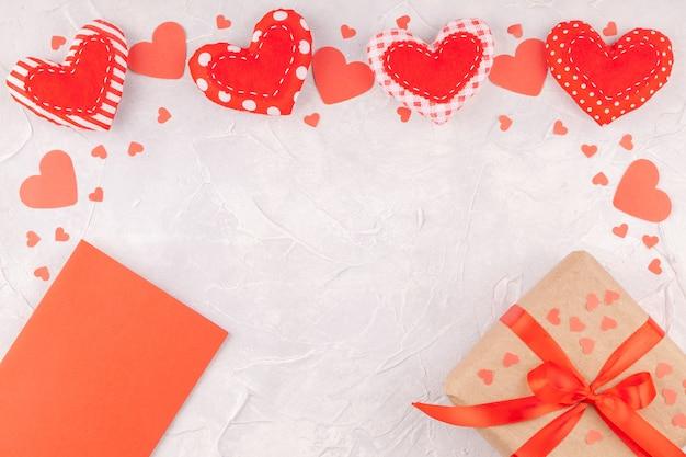 Fondo de san valentín con corazones, caja de regalo con cinta roja y tarjeta en blanco