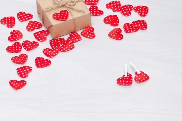 Fondo de san valentín corazones rojos con caja de regalo sobre fondo blanco de madera. día de san valentín, amor, concepto de boda. vista plana, vista superior.