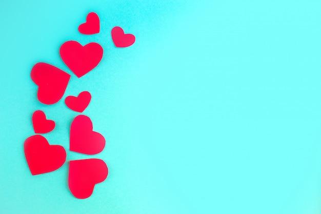 Fondo de san valentín. corazones rojos sobre fondo azul pastel. concepto de día de san valentín plano, vista superior, espacio de copia