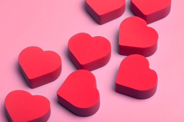 Fondo de san valentín. corazones rojos sobre un fondo rosa mínimo. concepto de amor, romance y corazones.