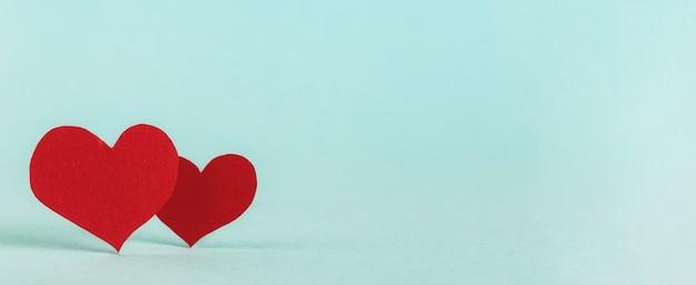 Fondo de san valentín. dos corazones de papel rojo sobre fondo azul pastel con espacio de copia