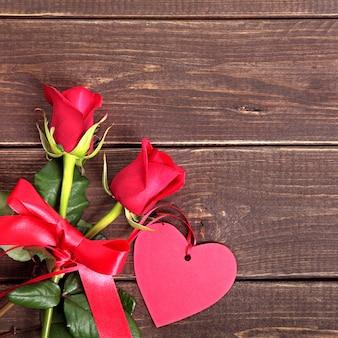 Fondo de san valentín de etiqueta de regalo y rosas rojas en madera