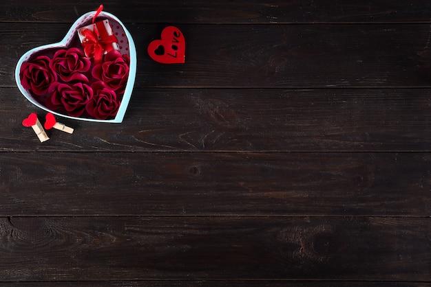Fondo de san valentín con mini regalo y rosa en caja de corazón