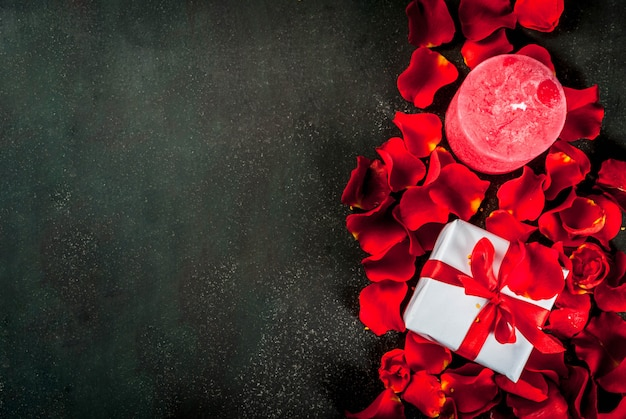 Fondo de san valentín con pétalos de rosa, caja de regalo envuelta en blanco con cinta roja y vela roja festiva, sobre fondo de piedra oscura, vista superior del espacio de copia