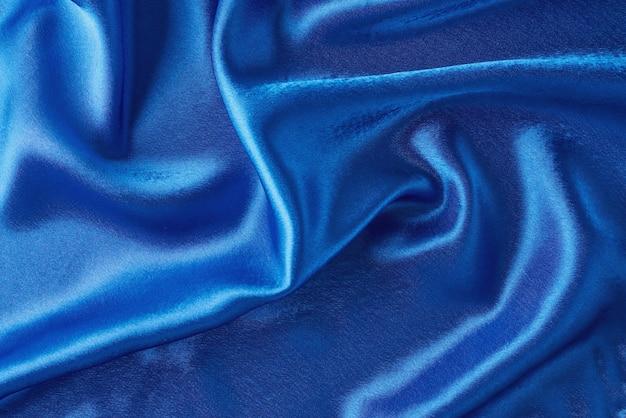 Fondo de seda azul con pliegues. textura abstracta de superficie satinada ondulada