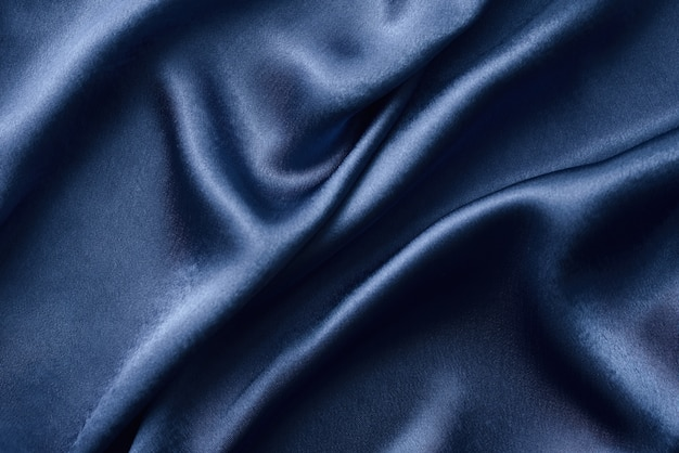 Fondo de seda plateado con pliegues. textura abstracta de la superficie de seda ondulada