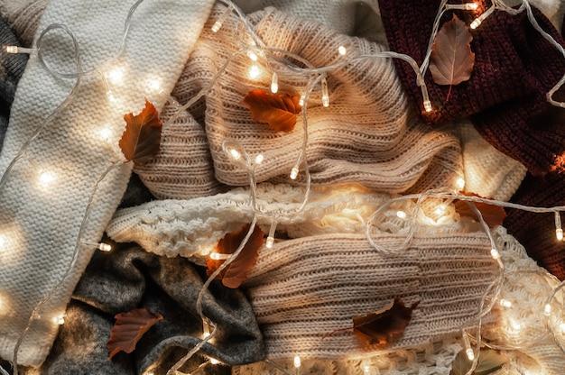 Fondo con suéteres calientes. montón de ropa de punto con hojas de otoño y una guirnalda.