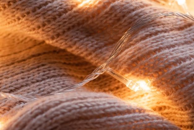 Fondo con suéteres calientes. ropa de punto con una guirnalda