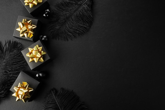 Fondo de super venta de viernes negro. cajas de regalo negras con cintas doradas y plumas.