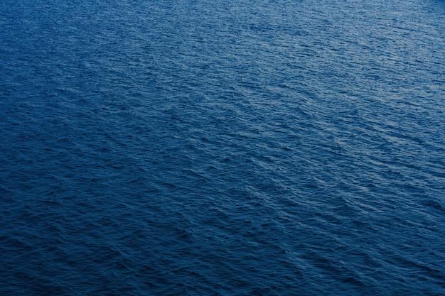 Fondo superficial abstracto del mar tranquilo o del agua del océano.