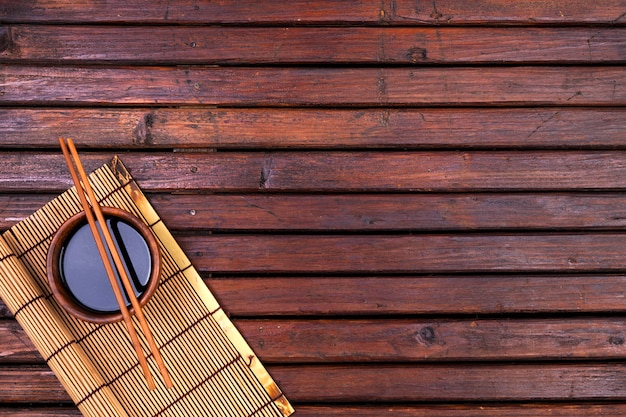 Fondo para sushi. estera de bambú, salsa de soja, palillos en la mesa de madera. vista superior y espacio de copia