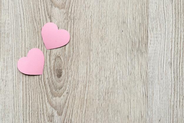 Fondo de tarjeta del día de san valentín, corazones lindos rosados de papel. fondo de madera con corazones en técnica de corte de papel. día de san valentín romántico.