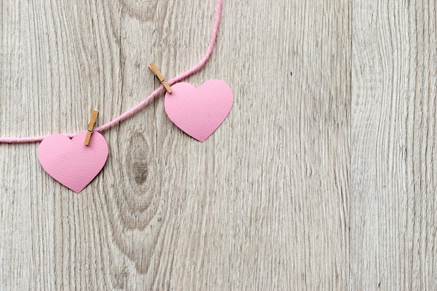 Fondo de tarjeta del día de san valentín, corazones lindos rosados de papel en una pinza para la ropa. fondo de madera con corazones en técnica de corte de papel. día de san valentín romántico.