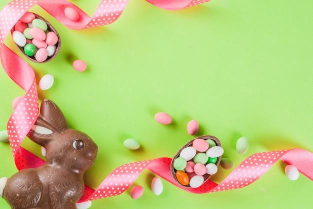 Fondo de tarjeta de felicitación de vacaciones de pascua, con conejito de pascua de chocolate, huevos de caramelo, huevos de codorniz y cinta festiva