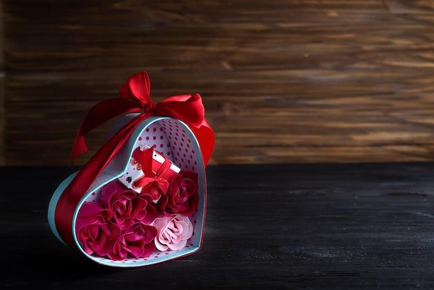 El fondo de las tarjetas del día de san valentín con los corazones rojos y se levantó en caja de regalo en fondo de madera oscuro
