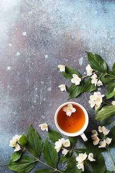 Fondo de té jazmín con tetera, hojas y flores de textura oscura, vista superior, espacio de copia, vertical