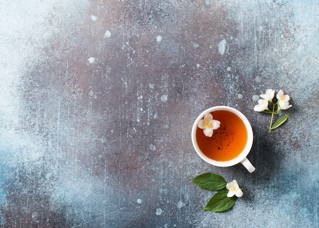 Fondo de té jazmín con tetera, hojas y flores de textura oscura, vista superior, espacio de copia
