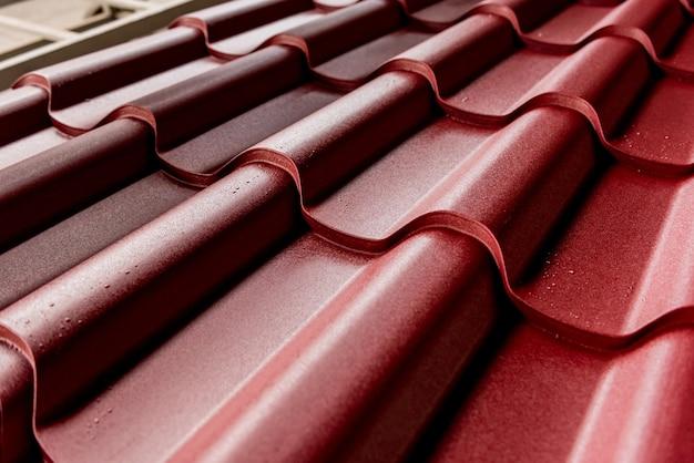 Fondo de tejas metálicas rojas con gotas de agua.