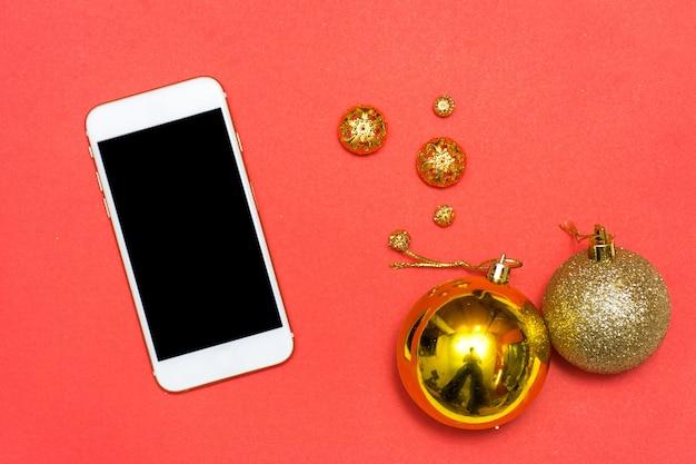 Fondo de teléfono inteligente de navidad o año nuevo: ramas de abeto, bolas de cristal de oro, decoración y conos sobre un fondo rojo