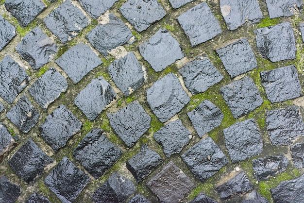 Fondo, textura, adoquines redondos de piedra gris vintage con gotas de lluvia
