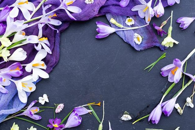 Fondo de textura negra con tela teñida de púrpura y flores de primavera
