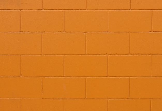 Fondo y textura de pared de ladrillo pintado de naranja