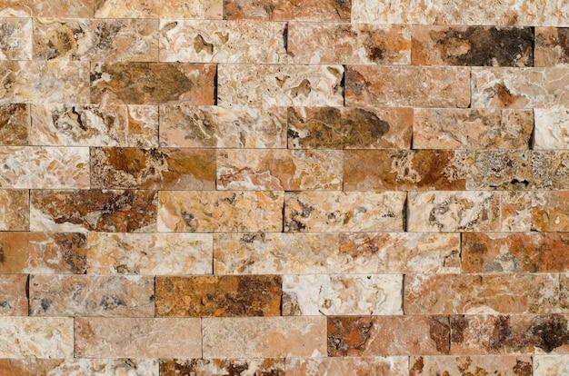 Fondo de una textura de revestimiento de pared de piedra, ladrillos de piedra marrón