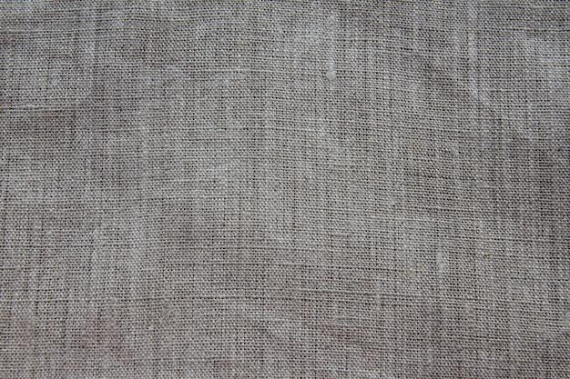 Fondo y textura de tela de lino gris con tejido cercano. ligeramente abollado