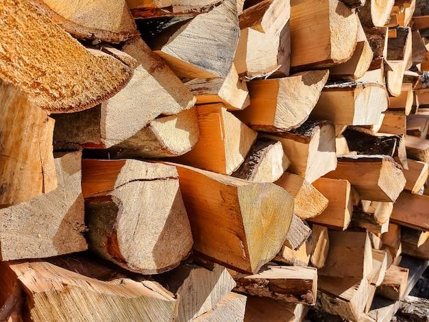 Fondo de troncos de leña seca picada apilados uno encima del otro en una pila. fila de caldo de leña para el invierno. enfoque selectivo. troncos de leña