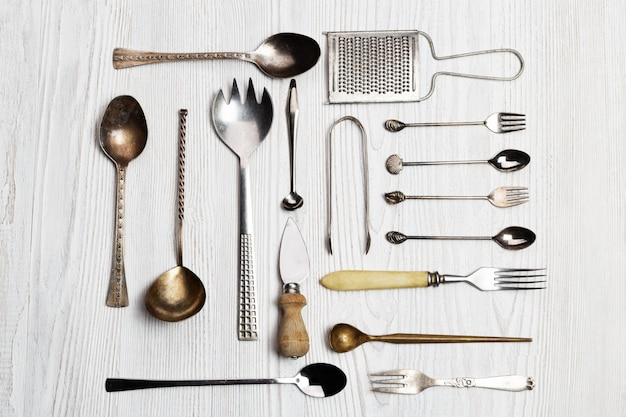Fondo de utensilios de cocina: cucharas, tenedores, cuchillo para queso, rallador, pinzas