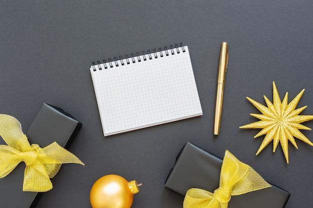 Fondo de vacaciones, fondo negro con estrella dorada brillante y cajas de regalo