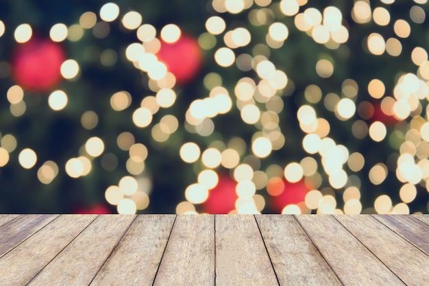 Fondo de vacaciones de navidad con mesa de madera vacía sobre luz festiva bokeh