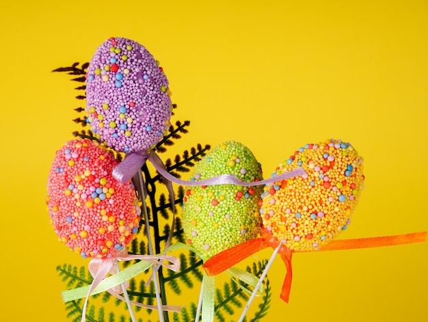 Fondo de vacaciones de semana santa. huevos de pascua adornados coloreados en un fondo amarillo brillante.
