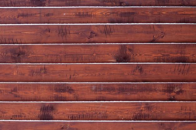 Fondo de valla de madera con nieve sobre los tableros
