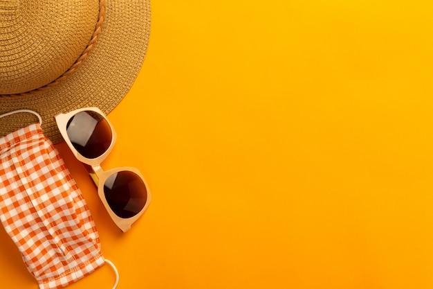 Fondo de verano con accesorios de playa: sombrero de paja, gafas de sol, máscara para evitar covid-19