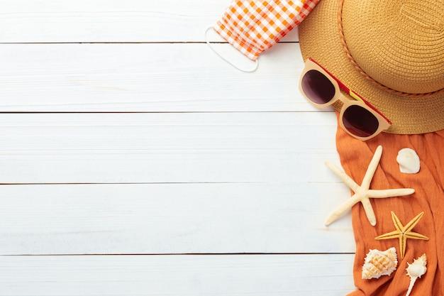 Fondo de verano con accesorios de playa: sombrero de paja, gafas de sol, toalla y máscara para evitar covid-19