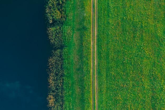 Fondo de verano desde arriba de un campo verde con una carretera y un lago
