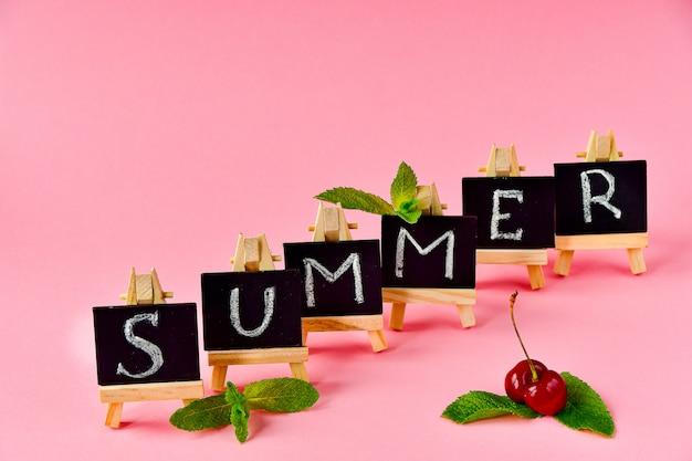 Fondo de verano rosa. tarjetas negras con letras de verano, hojas de menta y una cereza.