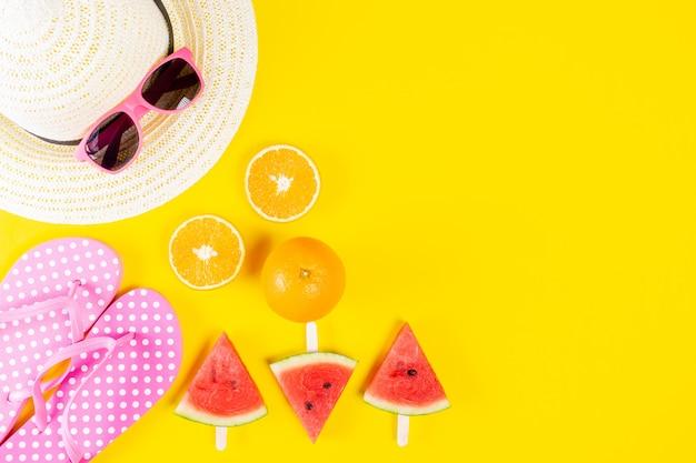 Fondo de verano sombrero, gafas de sol, chanclas, sandía y naranjas sobre fondo amarillo.