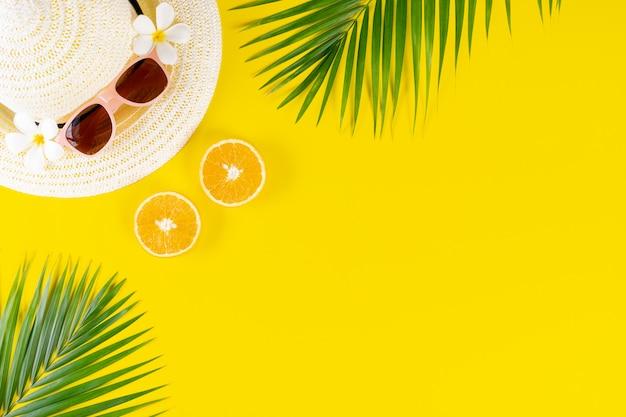 Fondo de verano sombrero, gafas de sol, hojas de palma y frutas sobre fondo amarillo.