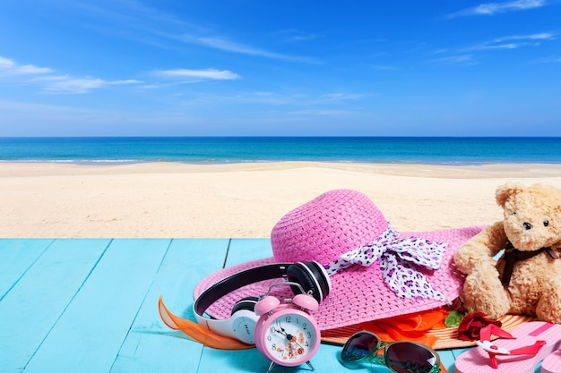 Fondo de verano de sombrero de playa y accesorios para vacaciones en tablón de madera